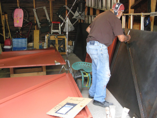 Joseph Vella painting the mural doors.
